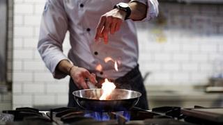 Kucharz gotujący na gazie w butli